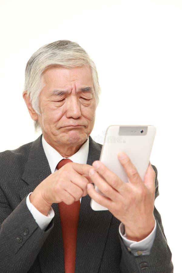 Homme d'affaires japonais sup?rieur utilisant la tablette semblant confuse photographie stock libre de droits