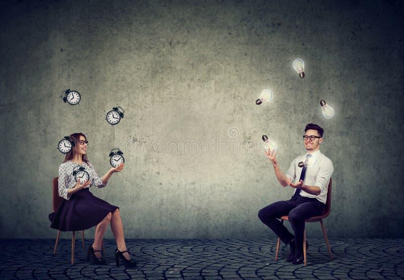 Homme d'affaires jonglant avec les ampoules d'idée avec du temps et l'efficacité de gestion de femme d'affaires photographie stock