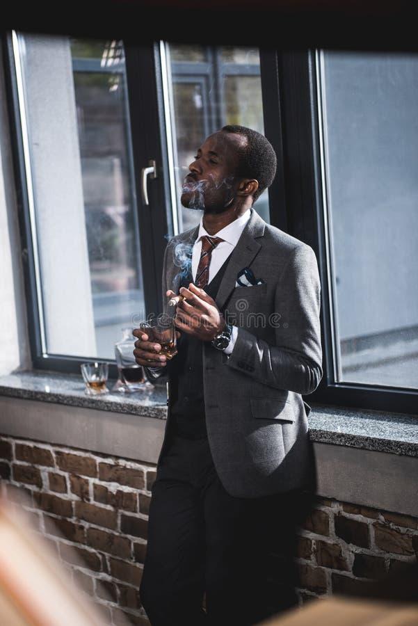Homme d'affaires jugeant de verre avec le whiskey et le cigare de tabagisme à l'intérieur photos stock