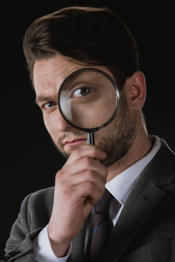 Homme d'affaires jugeant la loupe d'isolement sur le noir image libre de droits