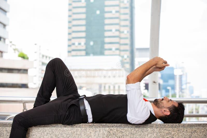 Homme d'affaires latin détendre pour fixer et jouer le smartphone image stock