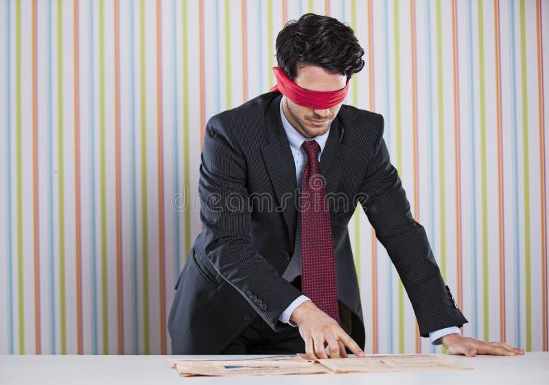 Homme d'affaires les yeux bandés lisant le journal images stock