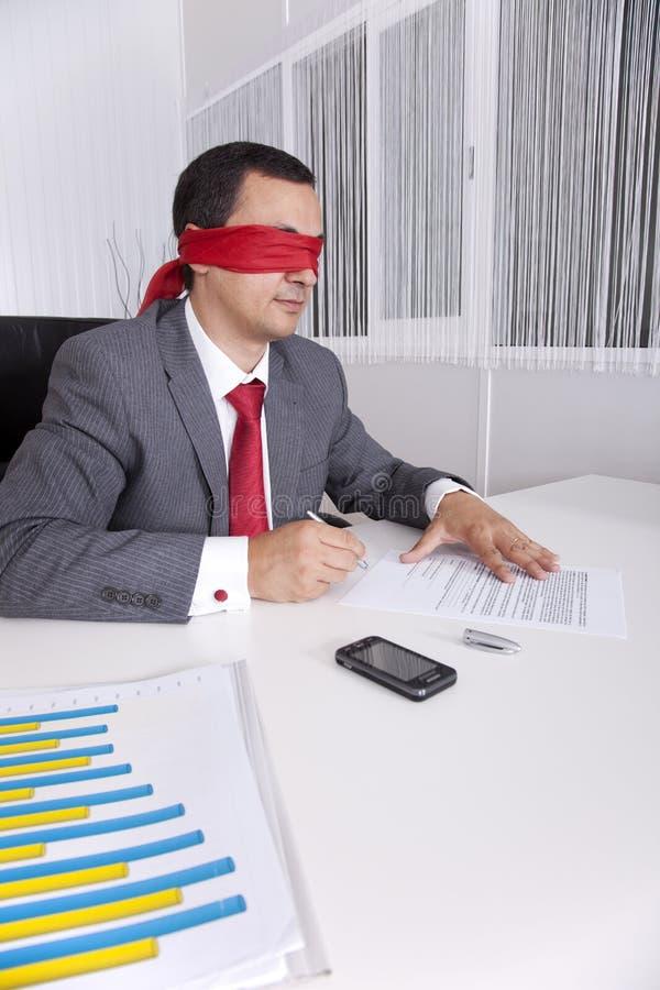 Homme d'affaires les yeux bandés travaillant avec son ordinateur portatif photo libre de droits