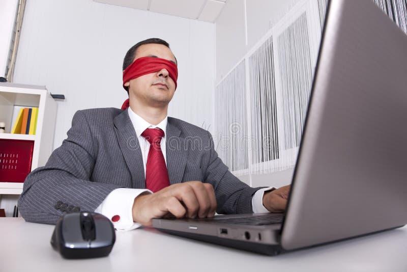 Homme d'affaires les yeux bandés travaillant avec son ordinateur portatif images stock
