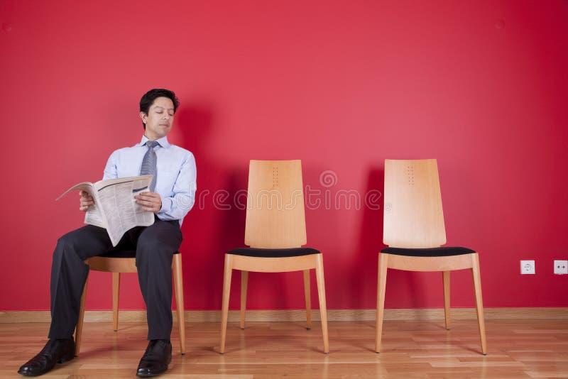 Homme d'affaires lisant un journal photos stock