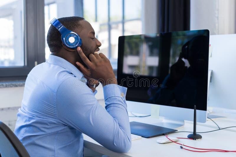 Homme d'affaires Listen To Music avec des écouteurs dans l'espace moderne de Coworking, homme adulte d'afro-américain d'affaires  photos libres de droits