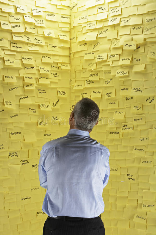 Homme d'affaires Looking At Wall couvert dans les notes collantes images stock