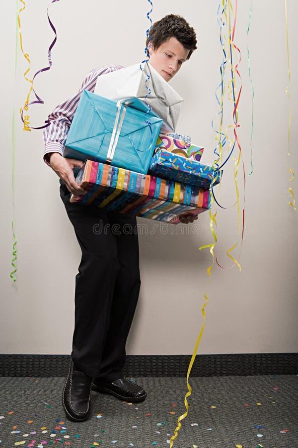 Homme d'affaires luttant avec la pile des présents image stock