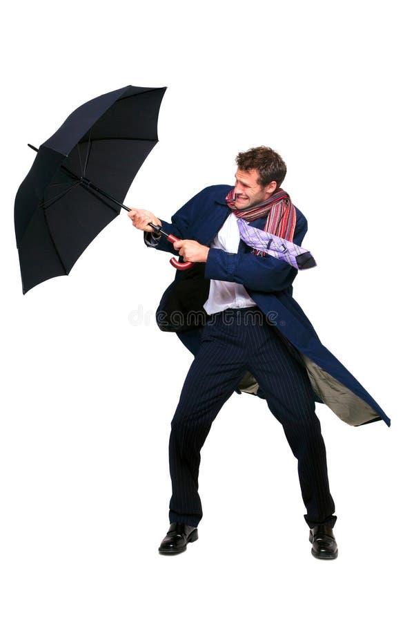 Homme d'affaires luttant avec le parapluie images libres de droits