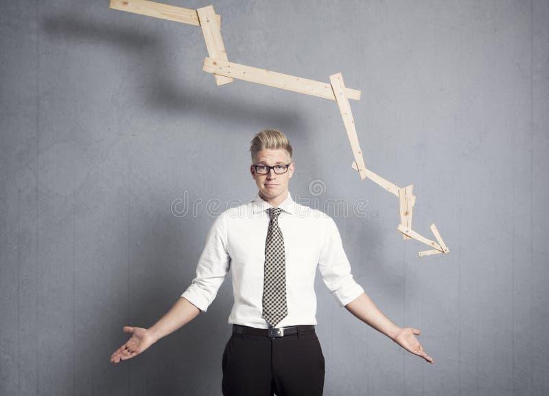 Homme d'affaires mécontent devant le graphique avec la tendance négative. photos libres de droits