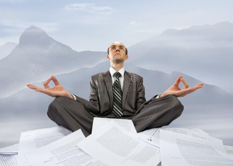 Homme d'affaires méditant en montagnes image libre de droits