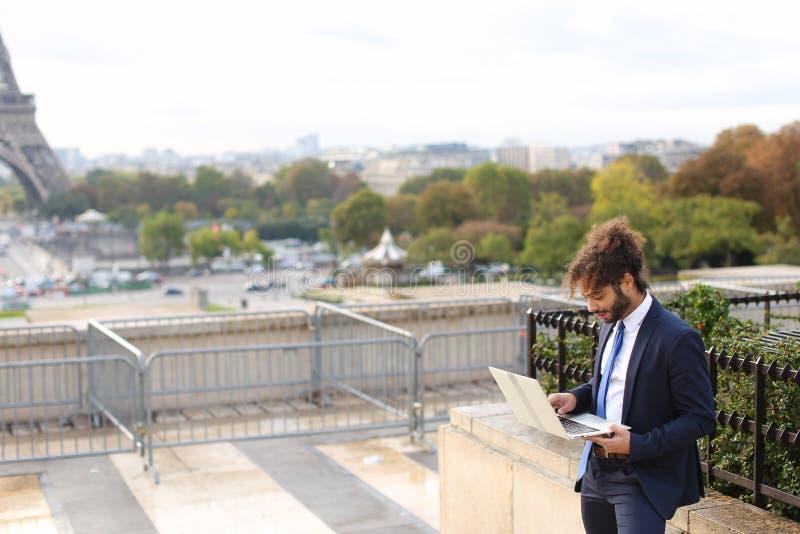 Homme d'affaires mélangé de sang travaillant avec l'ordinateur portable près de Tour Eiffel dedans images stock