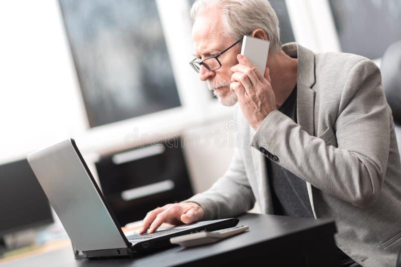 Homme d'affaires mûr à l'aide du téléphone portable et de l'ordinateur portable photographie stock libre de droits