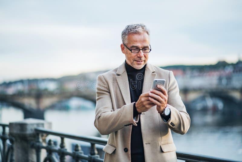 Homme d'affaires mûr avec la rivière se tenante prêt de smartphone dans la ville de Prague, prenant le selfie photographie stock libre de droits