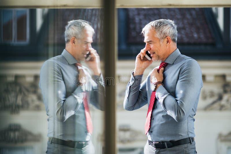 Homme d'affaires mûr avec le smartphone se tenant sur une terrasse dans la ville, faisant un appel téléphonique photographie stock libre de droits