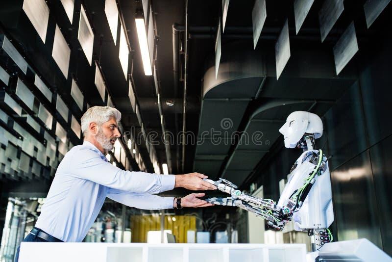 Homme d'affaires mûr ou un scientifique avec le robot photos stock