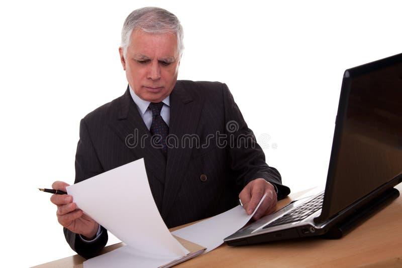 Homme d'affaires mûr regardant à l'ordinateur photographie stock libre de droits