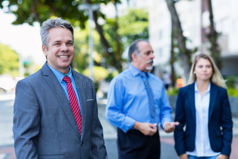 Homme d'affaires mûr riant avec le groupe d'hommes d'affaires images libres de droits