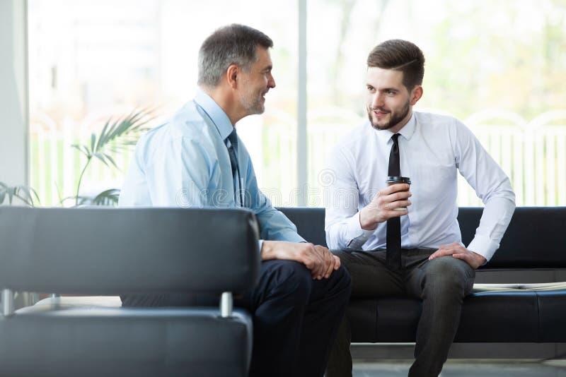 Homme d'affaires mûr utilisant un comprimé numérique pour discuter l'information avec un plus jeune collègue dans un salon modern images stock