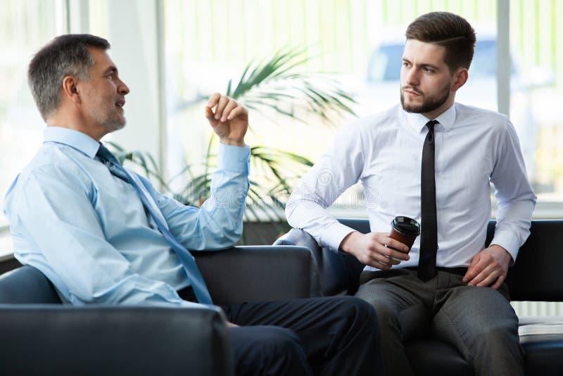 Homme d'affaires mûr utilisant un comprimé numérique pour discuter l'information avec un plus jeune collègue dans un salon modern image libre de droits