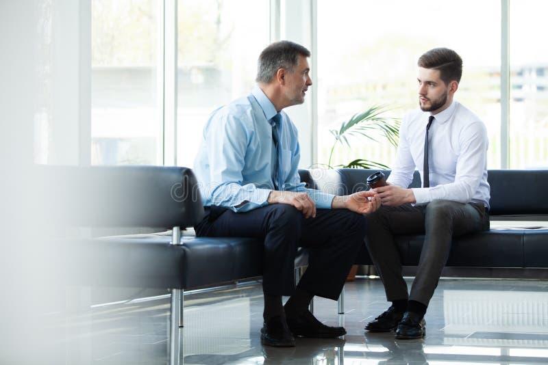 Homme d'affaires mûr utilisant un comprimé numérique pour discuter l'information avec un plus jeune collègue dans un salon modern images libres de droits