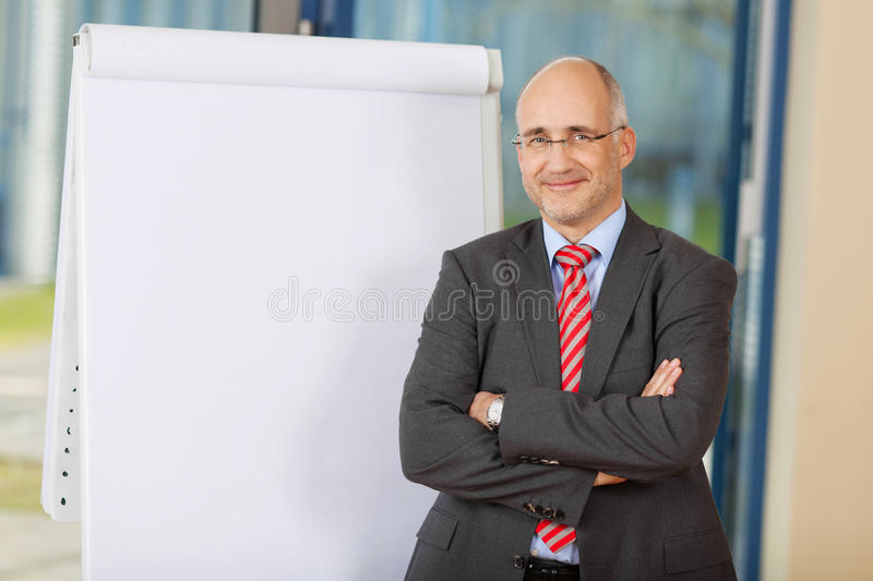 Homme d'affaires mûr With Arms Crossed se tenant prêt Flipchart photo stock