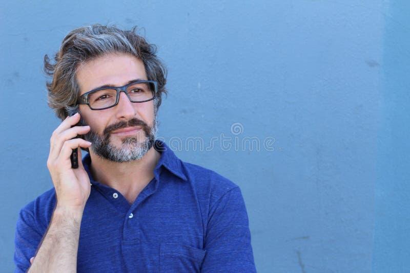 Homme d'affaires mûr de sourire parlant au téléphone portable avec l'espace de copie photo stock