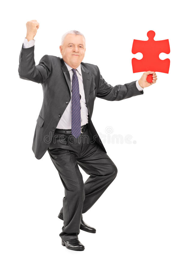 Homme d'affaires mûr joyeux tenant le morceau de puzzle photos libres de droits