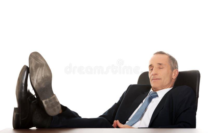 Homme d'affaires mûr se reposant dans le fauteuil photographie stock libre de droits