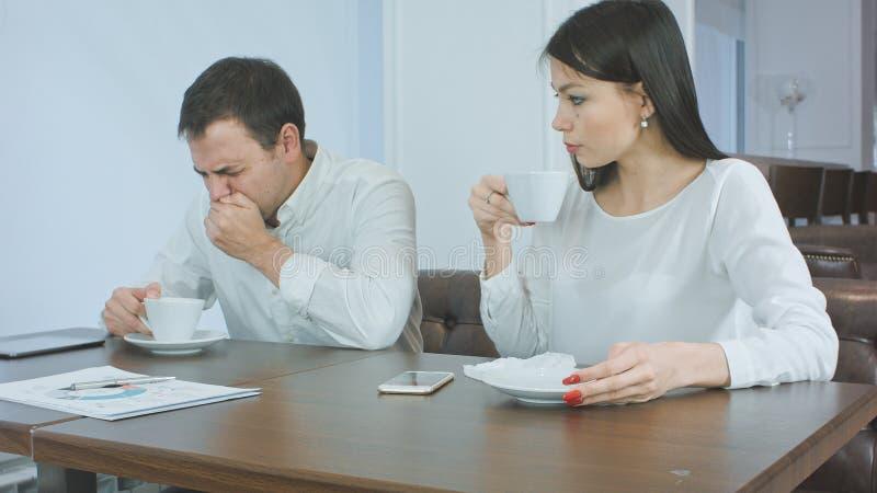 Homme d'affaires malade éternuant tandis que femelle soucieuse examinant sa tête pour déceler la fièvre et lui donnant la serviet photo libre de droits