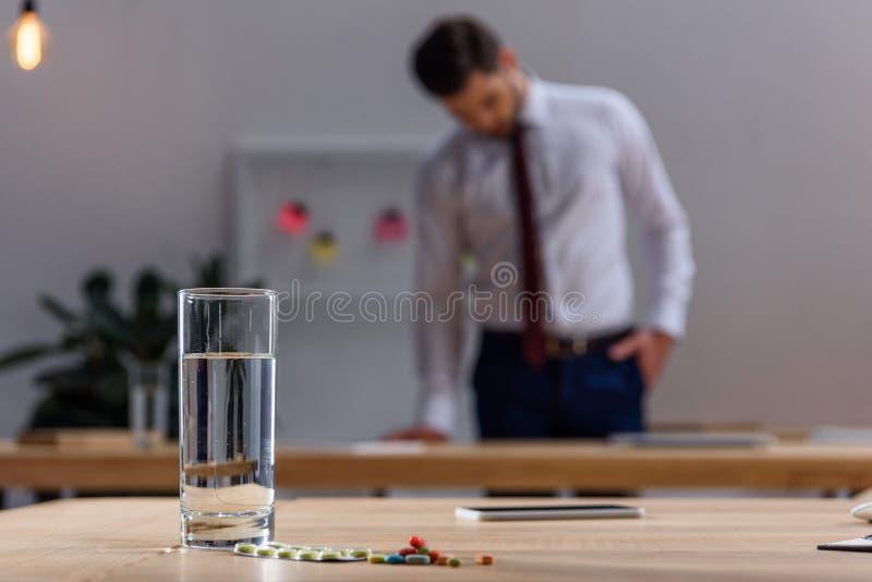 homme d'affaires malade se tenant dans le bureau avec des pilules sur la table image libre de droits