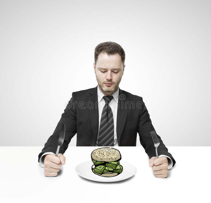 Homme d'affaires mangeant l'argent image stock