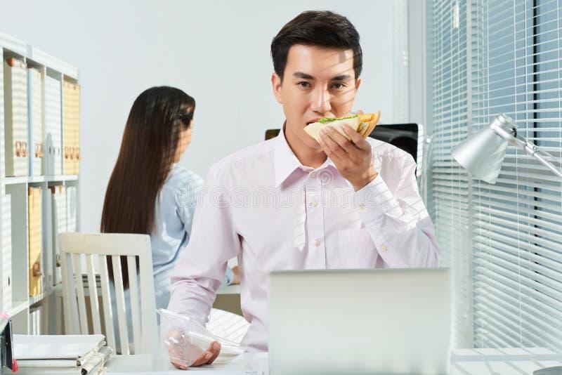 Homme d'affaires mangeant le sandwich images stock