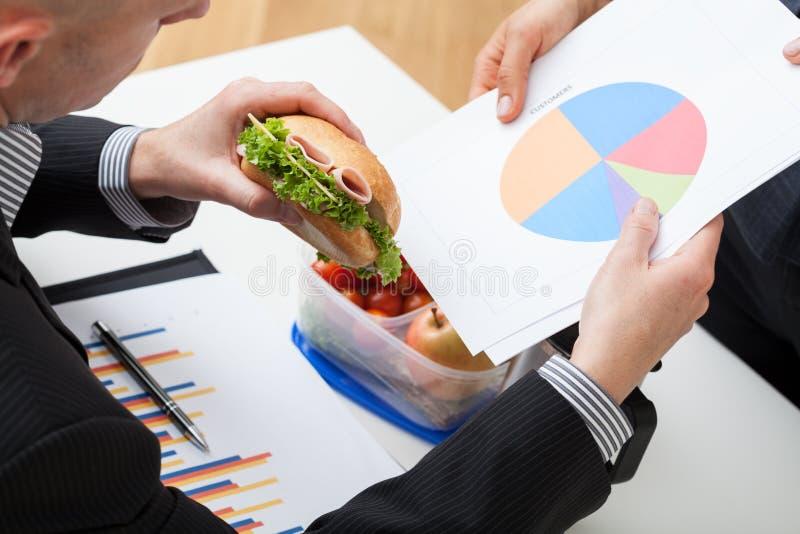 Homme d'affaires mangeant le sandwich pendant le travail photographie stock