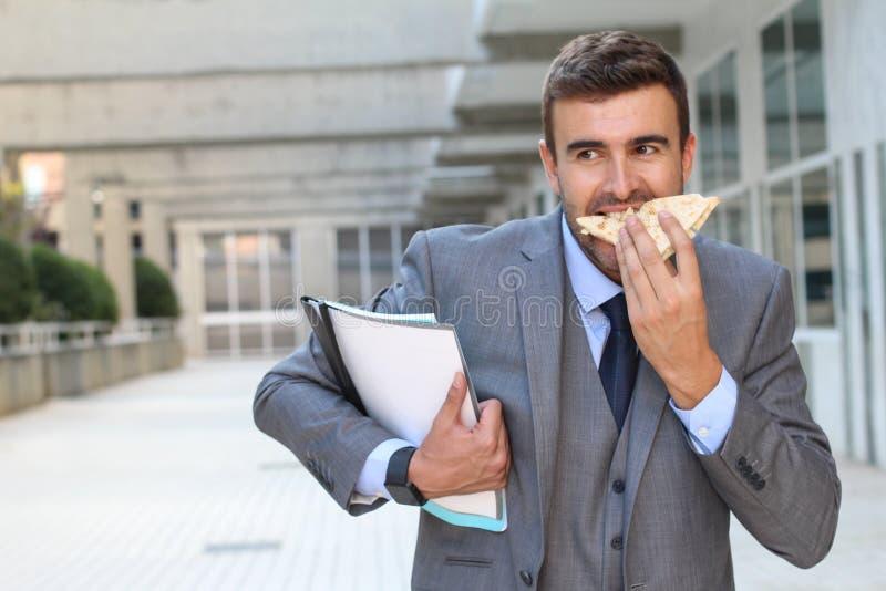 Homme d'affaires mangeant un sandwich sur l'aller images stock