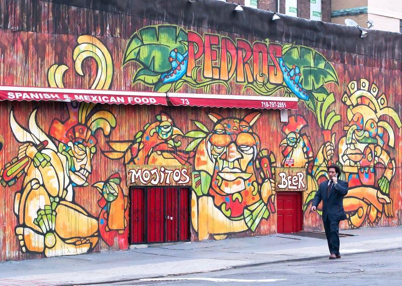 Homme d'affaires marchant devant un mur de graffiti à Brooklyn photographie stock libre de droits