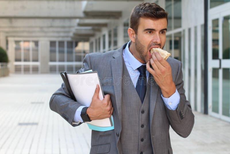 Homme d'affaires marchant et mangeant en même temps image stock