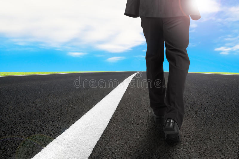 Homme d'affaires marchant sur la route goudronnée avec le ciel bleu de lumière du soleil photographie stock libre de droits