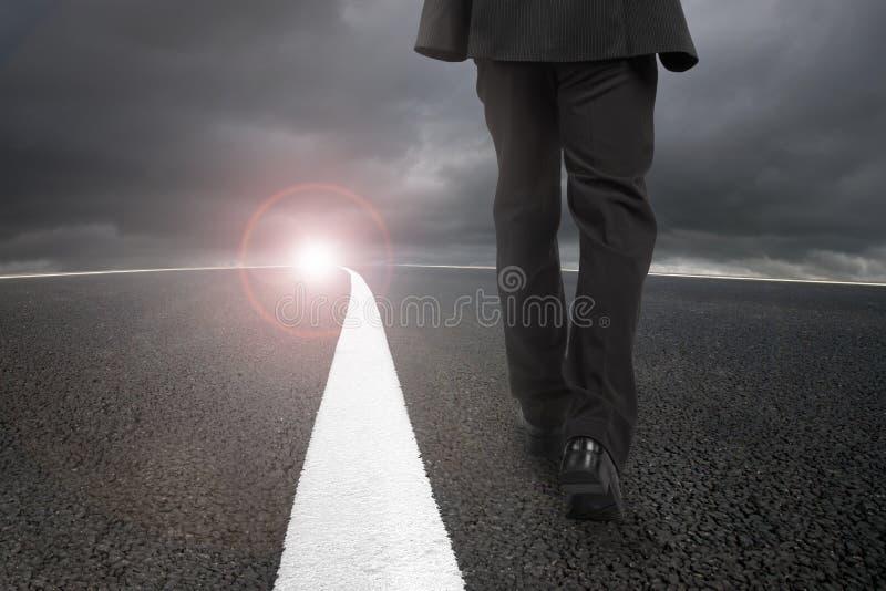 Homme d'affaires marchant sur la route goudronnée avec le ciel nuageux de lumière du soleil photo libre de droits