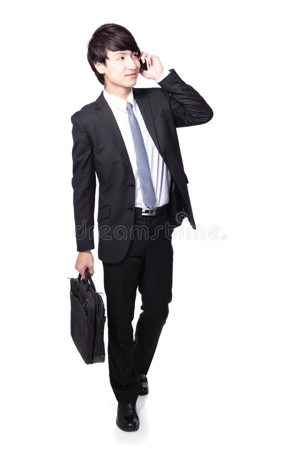 Homme d'affaires marchant tout en parlant le téléphone photographie stock