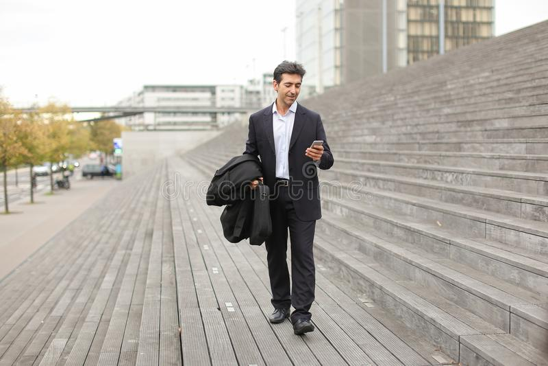 homme d'affaires marchant utilisant le smartphone pour observer des photos photo stock
