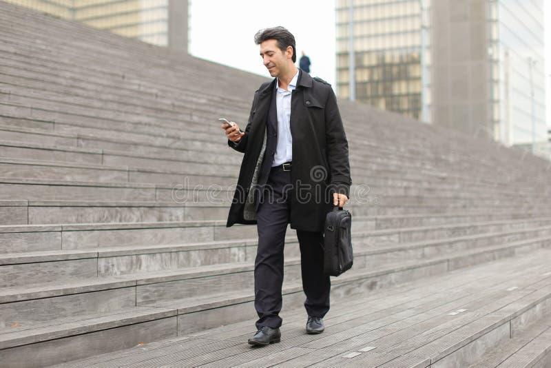 homme d'affaires marchant utilisant le smartphone pour observer des photos image stock