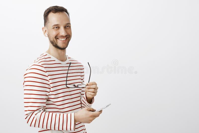 Homme d'affaires masculin réussi positif, enlevant des verres, le regard de côté et le sourire amical, sélectionnant la musique p photographie stock