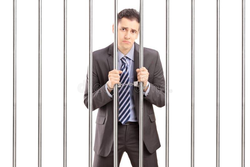 Homme d'affaires menotté triste dans le costume posant en prison et tenant le Ba photos stock