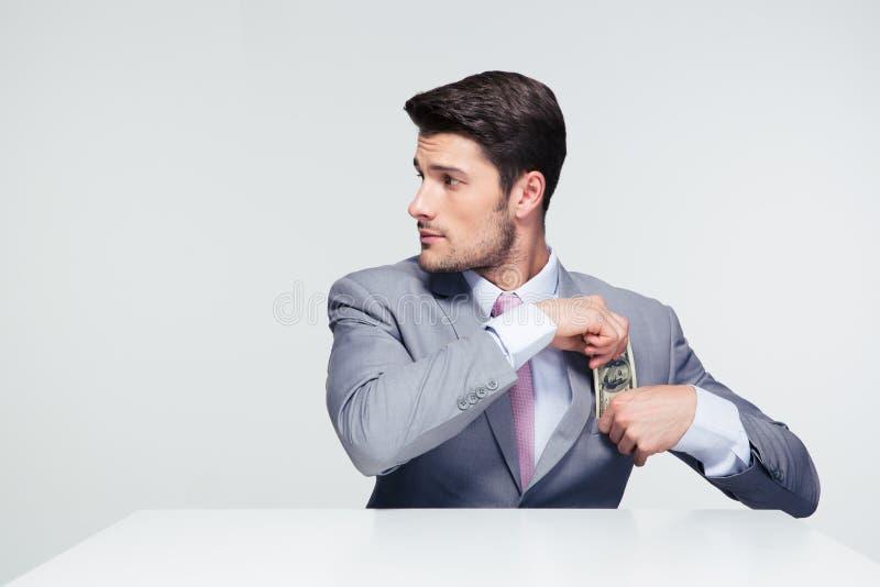 Homme d'affaires mettant l'argent dans la poche photos stock
