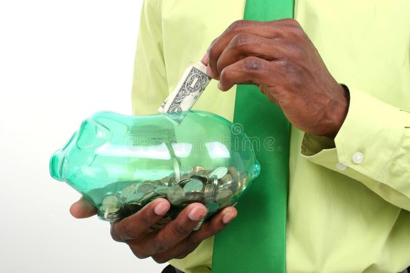 Homme d'affaires mettant un billet d'un dollar à la tirelire verte image stock