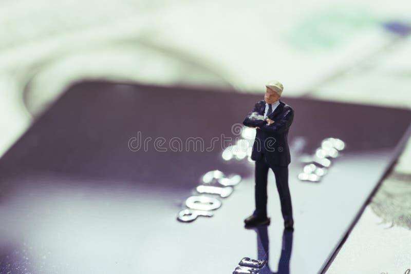 Homme d'affaires miniature dans le costume se tenant et pensant sur la carte de crédit employant en tant qu'achats en ligne, dett photos stock