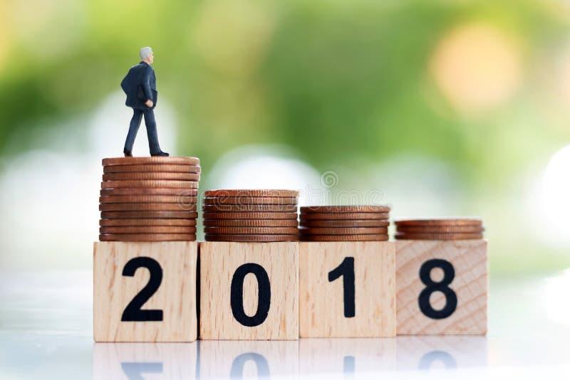 Homme d'affaires miniature se tenant sur l'étape de l'argent de pièce de monnaie avec le bloc numéro 2018 images stock