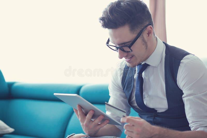 Homme d'affaires moderne avec la carte de crédit et le comprimé photographie stock