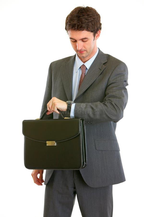 Homme d'affaires moderne avec la serviette contrôlant le temps photos stock